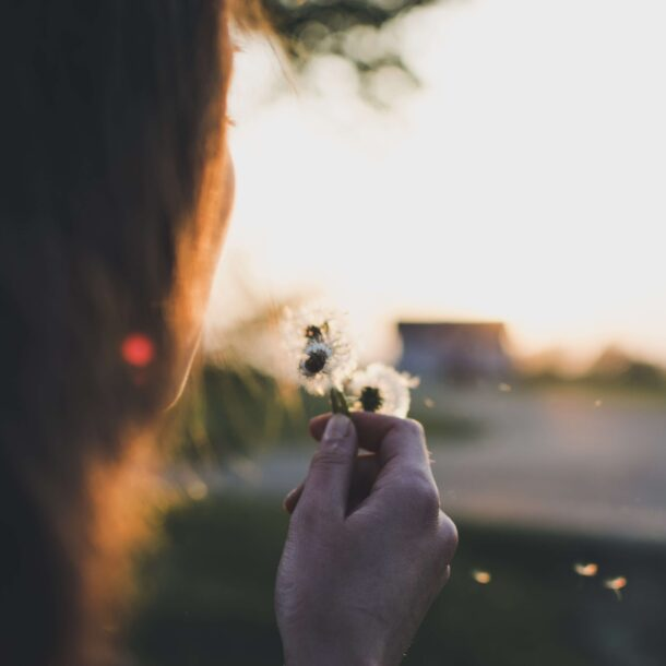 Woman breathing on flower