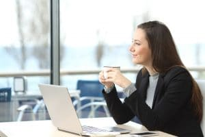 smiling-woman-at-desk-with-coffee-shutterstock-389992177_1_orig